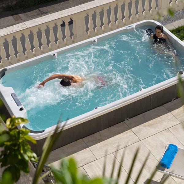 lui fa allenamento a casa in una mini piscina nuoto controcorrente mentre lei lo guarda